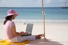 Asiatische Frau, die an dem Strand arbeitet Lizenzfreies Stockbild