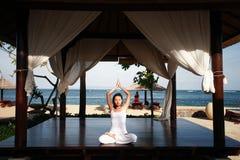 Asiatische Frau, die durch den Strand meditiert Stockbilder