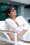 Asiatische Frau, die ein sunbed durch Pool sich entspannt Lizenzfreie Stockbilder