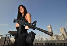 Asiatische Frau, die eine übersehenstadt des Mittelgewehrs anhält Stockbilder