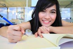 Asiatische Frau, die eine Anmerkung in das Büro schreibt Stockfotografie