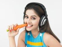 Asiatische Frau, die eine Karotte isst Stockbilder