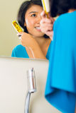 Asiatische Frau, die Haar im Badezimmerspiegel kämmt Lizenzfreie Stockfotos