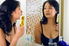 Asiatische Frau, die Haar im Badezimmerspiegel kämmt Stockbild