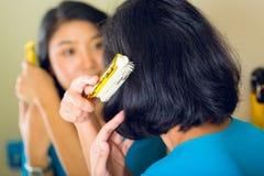 Asiatische Frau, die Haar im Badezimmerspiegel kämmt Stockbilder