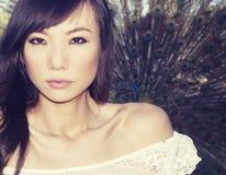 Asiatische Frau, die neben Pfau aufwirft Lizenzfreies Stockfoto