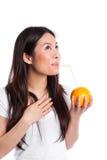 Asiatische Frau, die Orangensaft trinkt Stockbild