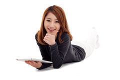 Asiatische Frau, die sich mit Tablette PC hinlegt und Daumen zeigt. Lizenzfreie Stockbilder