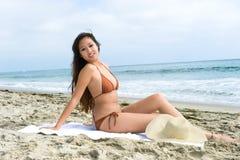 Asiatische Frau, die am Strand ein Sonnenbad nimmt stockfotografie