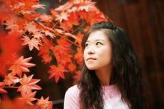 Asiatische Frau im roten Herbst lizenzfreie stockfotos