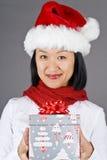 Asiatische Frau im Sankt-Hut, der ein Weihnachtsgeschenk anhält Lizenzfreies Stockfoto