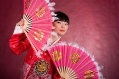 Asiatische Frau im traditionellen Kleid mit dem Gebläse Stockbild