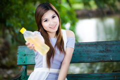 Asiatische Frau mit einer Flasche Wasser im Park Stockfotos
