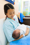 Asiatische Frau mit neugeborenem in den Armen Stockfotografie