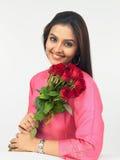 Asiatische Frau mit roten Rosen Stockfotografie