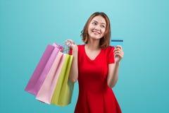 Asiatische Frau Sankt, die Einkaufstaschen und Kreditkarte gegen hält Stockfoto