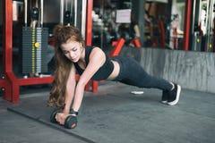 Asiatische Frauenübung der jungen Eignung und Handeln von Plankenposition mit stockbilder