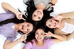 Asiatische Frauen, die das lächelnde Lügen auf dem Boden sich entspannen Stockfoto