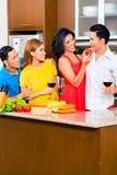 Asiatische Freunde, die für Abendessen kochen Stockfoto