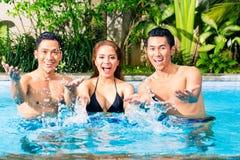 Asiatische Freunde, die im Pool schwimmen lizenzfreie stockbilder