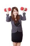 Asiatische Geschäftsfrauübung mit Dummköpfen in ihren beiden Händen Lizenzfreie Stockfotografie