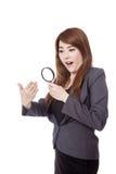 Asiatische Geschäftsfrau überraschte aufpassende Hand der Gebrauchslupe Lizenzfreie Stockfotos