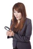 Asiatische Geschäftsfrau überraschte Gebrauchslupe, die unten schaut Lizenzfreies Stockfoto
