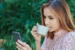 Asiatische Geschäftsfrau arbeitet unter Verwendung des Mobiles und Note intelligenten pho lizenzfreie stockfotografie