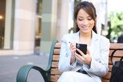 Asiatische Geschäftsfrau auf Bank außerhalb des Büros Lizenzfreies Stockfoto