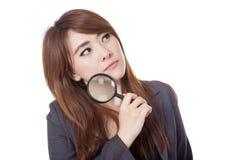 Asiatische Geschäftsfrau denkt mit der Lupe, die u schaut Lizenzfreie Stockfotos