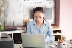 Asiatische Geschäftsfrau der neuen Generation unter Verwendung des Laptops im Büro, Asiatinnen, die das Lächeln beim Arbeiten auf lizenzfreies stockfoto