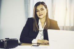 Asiatische Geschäftsfrau des Porträts mit VR und intelligente Telefone auf Tabelle, mit den Verkäufen von VR-Kopfhörer in der Wel lizenzfreie stockfotografie