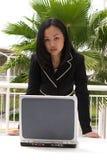 Asiatische Geschäftsfrau, die über Laptop schaut Stockfotos