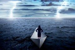 Asiatische Geschäftsfrau, die allein auf dem Papierboot steht Stockbilder