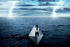 Asiatische Geschäftsfrau, die allein auf dem Papierboot steht Lizenzfreies Stockfoto