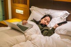 Asiatische Geschäftsfrau, die auf Hotelbett müde und geschlafen worden sein würden stockfotos