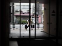 Asiatische Geschäftsfrau, die auf städtische Straße beim Halten eines Pöbels geht lizenzfreies stockfoto