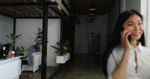 Asiatische Geschäftsfrau, die beim Telefonanruf verwahrt Dokumente in der schönen Geschäftsfraufunktion des modernen kreativen Bü stock footage