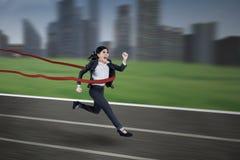 Asiatische Geschäftsfrau, die das Rennen gewinnt stockfotografie