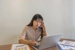 Asiatische Geschäftsfrau, die Daten bezüglich des Laptops betrachtet Lizenzfreie Stockbilder