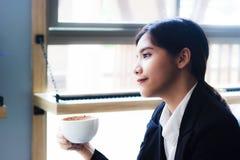 Asiatische Geschäftsfrau, die in der Kaffeestube mit heißem Kaffee sich entspannt stockbild