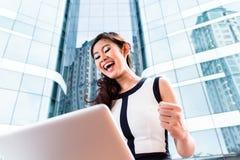 Asiatische Geschäftsfrau, die draußen an Computer arbeitet Lizenzfreies Stockfoto