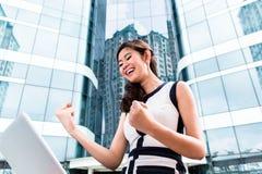 Asiatische Geschäftsfrau, die draußen an Computer arbeitet Lizenzfreie Stockfotos