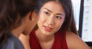 Asiatische Geschäftsfrau, die eine Diskussion mit mexikanischem Kollegen hat lizenzfreies stockfoto