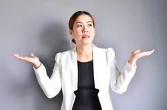 Asiatische Geschäftsfrau, die ihre Hände auf beiden Seiten auf grauem BAC anhebt Stockbilder