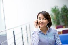 Asiatische Geschäftsfrau, die an ihrem Schreibtisch in einem Büro sitzt Stockbild