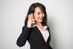 Asiatische Geschäftsfrau, die intelligentes Telefon verwendet Das Lächeln und das Schauen kamen stockfotografie