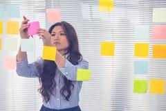 Asiatische Geschäftsfrau, die klebrige Anmerkungen über Wand verwendet Lizenzfreie Stockbilder