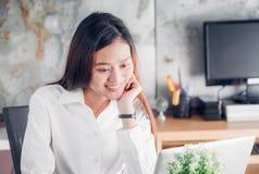 Asiatische Geschäftsfrau, die Laptop-Computer und lächelndes Gesicht betrachtet Lizenzfreie Stockbilder