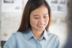 Asiatische Geschäftsfrau, die Laptop-Computer und lächelndes Gesicht betrachtet Stockfotografie